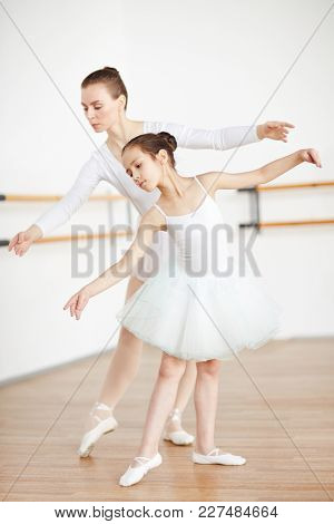 Adorable girl and her ballet teacher stretching their arms and right legs altogether