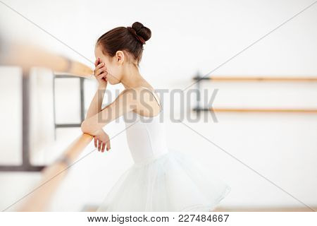 Sad little girl in ballet dress crying by wooden bars during class