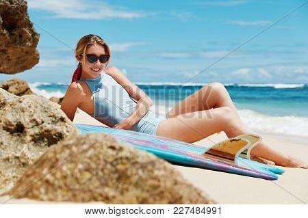 Photo Of Pleasant Looking Young Female In Shades And Swimsuit, Lies On Hot Sand Near Ocean, Poses At