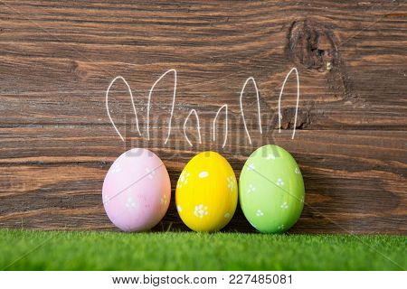 Colorful Easter Eggs On Grass With Painted Rabbit Ears On Wooden Background.