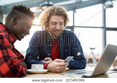 Intercultural employees in casualwear spending time in cafe by cup of coffee and watching video in smartphone