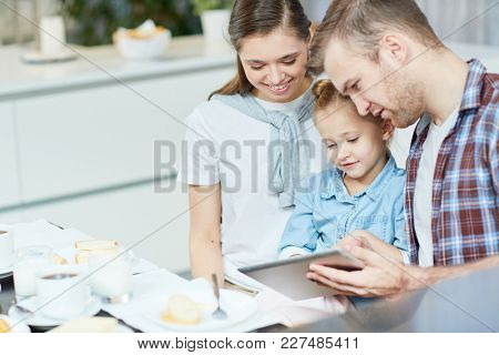 Young parents showing their cute daughter online information about usage of healthy food during breakfast