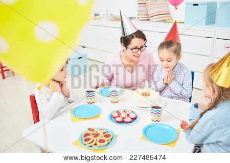 Adorable child making wish while looking at burning candles on birthday cake at party