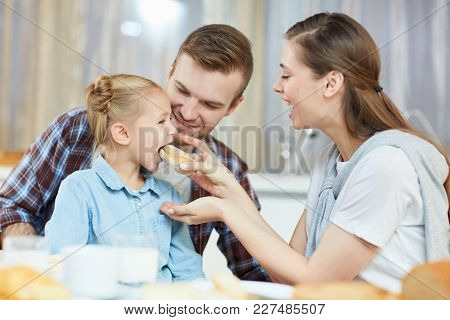 Young mother taking care of little daughter while feeding her with fresh homemade pastry
