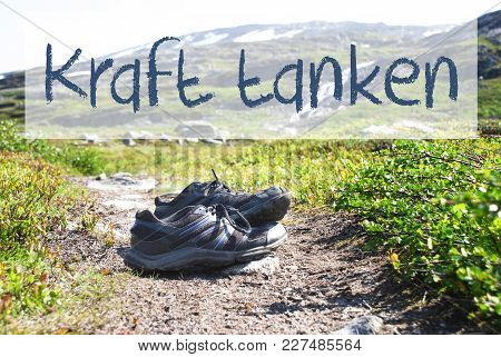 German Text Kraft Tanken Means Relax. Trekking Shoes On Hiking Path In Norway. Mountains In The Back