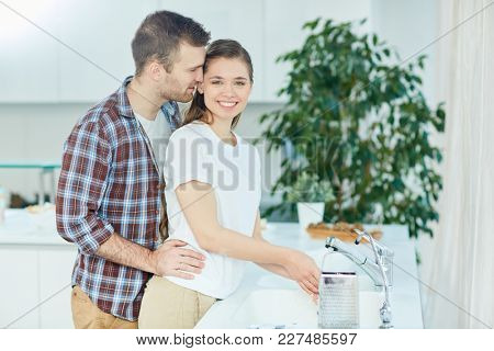 Young woman washing her hands in the kitchen while amorous husband embracing her