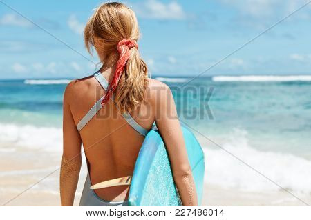 Active Female Surfer In Swimsuit Enjoys Perfect Sunny Day On Beach, Looks At Beautiful Ocean View, H