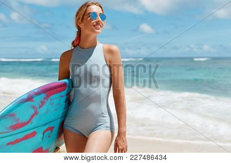 Sporty Young Blonde Female With Perfect Fit Body, Wears Swimsuit And Shades, Carries Surf Board, Has
