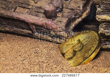 The Gold Coin Of The Crypto Currency Bitcoin Lies In The Sand Near The Wrecked Ship That Was Shipwre
