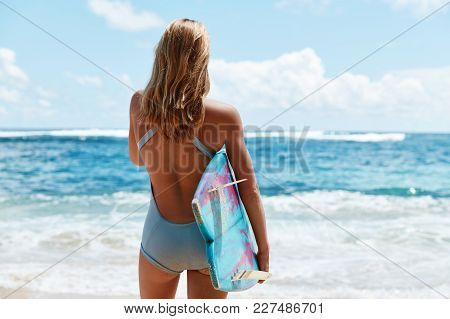 Shot Of Slim Sporty Woman Stands Back, Holds Surf Board Under Arm, Admires Beautiful Ocean View And