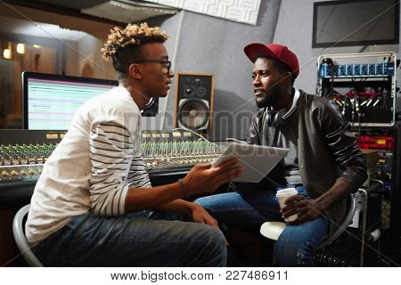 Conversation of young deejay with tablet and modern musician discussing new trends in world music