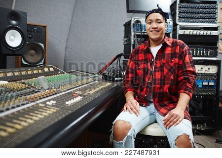 Happy sound operator sitting in studio of audio records by switchboard