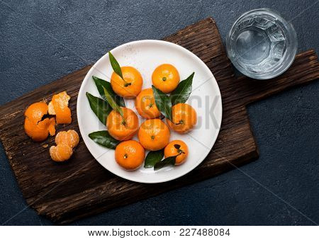 Tangerines with leaves on the plate over rustic wooden cutting board and dark background, copy space. Top view