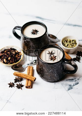Two big ceramic cups of hot tea with milk and spices. Hot drink for a cold season.