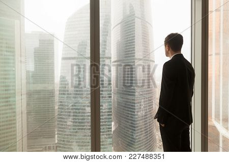 Man In Business Suit Standing With Hands In Pants Pockets Looking Through Window On City Landscape W
