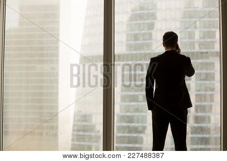 Businessman Talking On Cellphone While Standing Neal Large Window In Office And Looking On Urban Lan