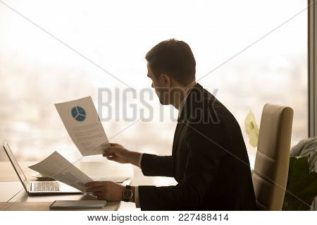 Businessman Studying Financial Documents, Reading Company Annual Report, Analyzing Profitability Sta