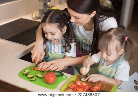 Mum Chopping Vegetables With Two Kids Daughters In Family Home Kitchen.