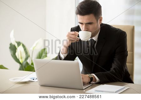 Successful Businessman Drinking Coffee While Working On Laptop In Office. Serious Company Ceo Enjoyi