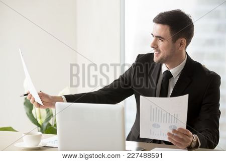 Smiling Businessman Looking At Business Documents With Positive Indicators, Enjoying Company Financi