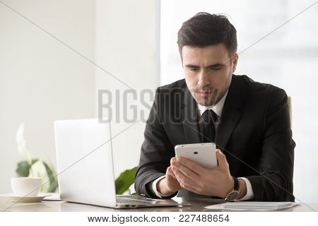 Serious Businessman Sitting At Desk With Laptop And Using Digital Tablet. Executive Manager Reading