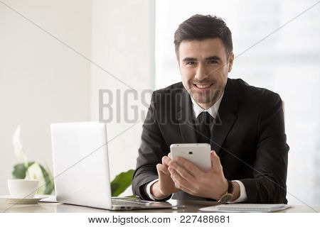 Portrait Of Handsome Businessman Sitting At Desk In Front Of Laptop, Using Digital Tablet And Lookin