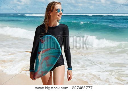Glad Positive Young Woman In Black Swimsuit, Looks Away With Happy Expreesion, Carries Surf Board, R