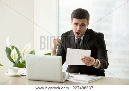 Excited Businessman Yelling With Joy When Reading Important Written Notification Or Letter At Desk I