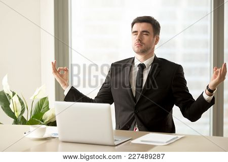 Handsome Man In Business Suit Meditating With Closed Eyes At Work Desk With Laptop. Successful Busin