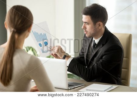 Male Financial Adviser Showing Document With Profitability Forecast To Female Client. Bank Employee