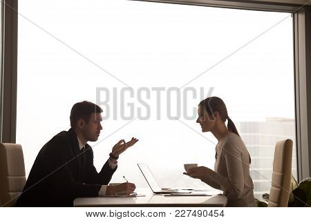 Businessman Explaining Interesting Idea To Female Colleague Sitting Opposite At Office Desk With Cup