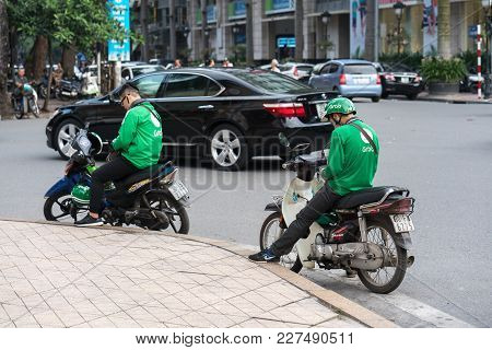 Hanoi, Vietnam - July 7, 2017: Grab Motorbike Driver Waiting For Customer On Ba Trieu Street. Entere