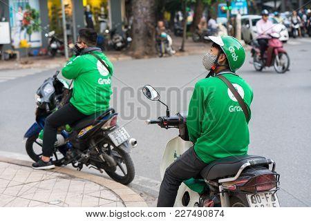 Hanoi, Vietnam - July 7, 2017: Grab Motorbike Driver Waiting For Customer On Ba Trieu Street. Entere