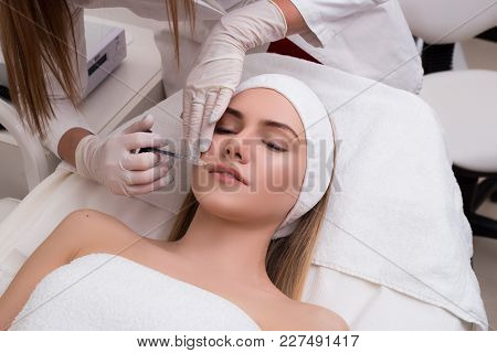 Save Your Youth! Beautiful Young Woman Getting Cosmetic Treatment Indoors As A Beauty Hyaluronic Lip