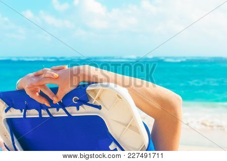 A Girl On A Deck Chair Lies On The Beach Of Punta Cana In The Dominican Republic.