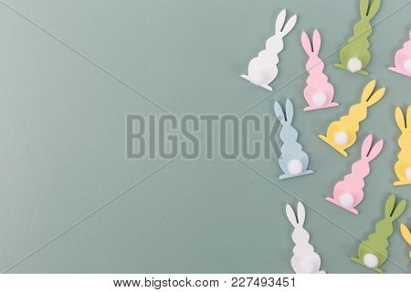 From Above Shot Of Composed Colorful Figurines Of Bunny Above Simple Background.