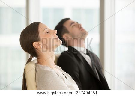 Satisfied Relaxed Businesswoman And Businessman Resting While Sitting On Chairs With Closed Eyes, Ta