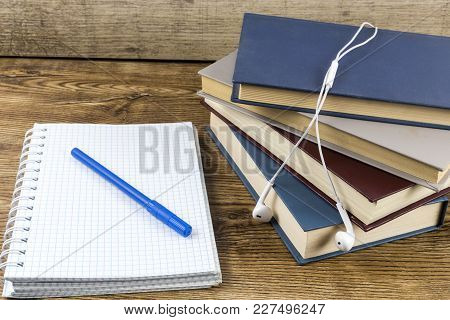 Blank Notebook With Pen, Books Earphone On Wooden Table.