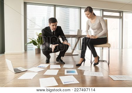 Experienced Male And Female Interior Designers Examining Apartment Drawings, Picking Colors, Analyzi