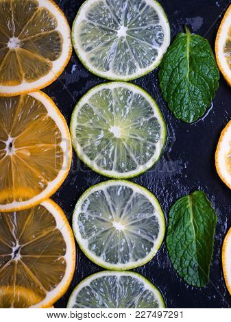 Citrus fruits. Limes and lemons slices over dark slate background