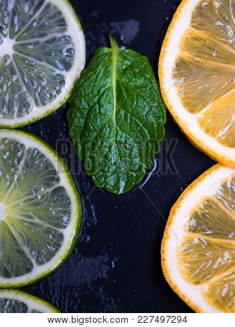 Citrus fruits. Limes and lemons slices with fresh mint over dark slate background
