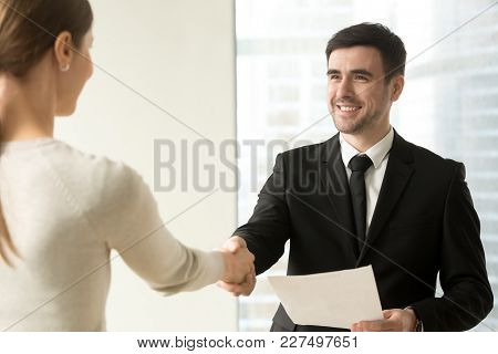 Smiling Male Manager With Contract Document In Hand Handshaking With Female Client Or Business Partn