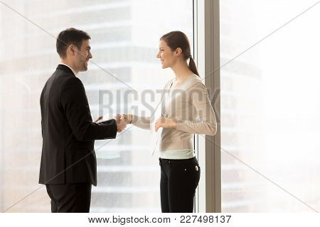 Friendly Smiling Female And Male Business Partners Handshaking Standing Near Window. Company Office