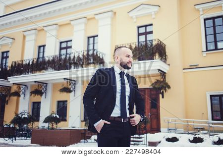 Handsome Man With Short Hair Wearing Classic Black Suit And Tie Posing Near Building. Classic Style.