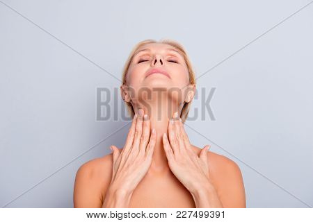 Portrait Of Pretty, Charming, Attractive Woman Enjoying Her Perfect Skin Holding Two Hands On Neck,