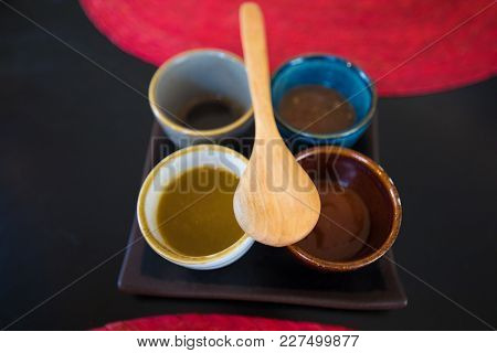 Four Sauces In Bowls With Wooden Spoon