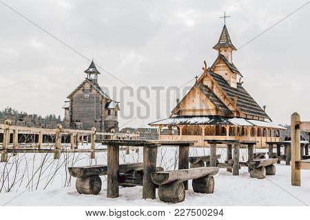 Old Wooden Table With Benches In Front Of Ancient Wooden Slavic Church On A Snowy Landscape. Histori
