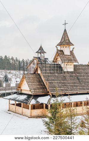 Ancient Wooden Slavic Church On A Snowy Landscape. Historical And Architectural Museum In The Open A