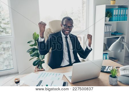 Attractive, Cheerful, Laughing, Multiethnic Accountant With Raised Fists Celebrating Sucessfuly Comp