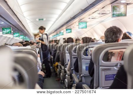 Interior Of Commercial Airplane With Flight Attandant Serving Passengers On Seats During Flight. Ste